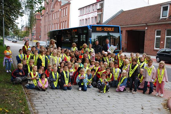 Kinder vor Einsteigerbus auf dem 'Bus-Schule' steht